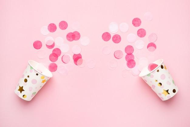 Copos de papel ecológico com confete rosa sobre fundo de cor rosa estilo mínimo plano leigos composição para aniversário dia das mães ou feriado de casamento