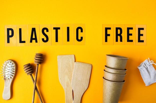Copos de papel ecológicos, utensílios de cozinha de madeira, escova de cabelo em fundo amarelo