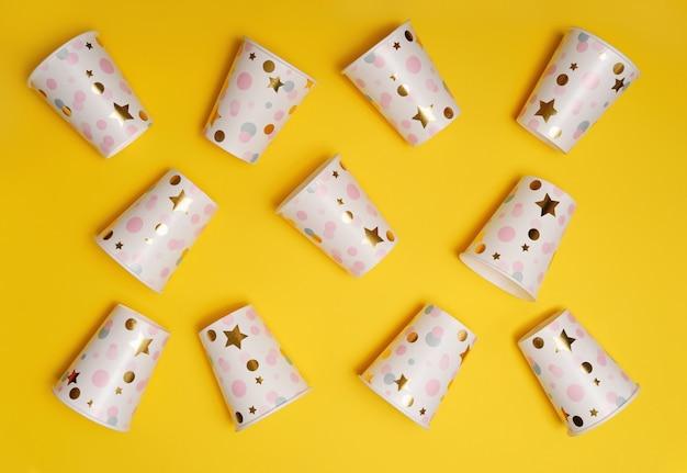 Copos de papel em fundo amarelo.