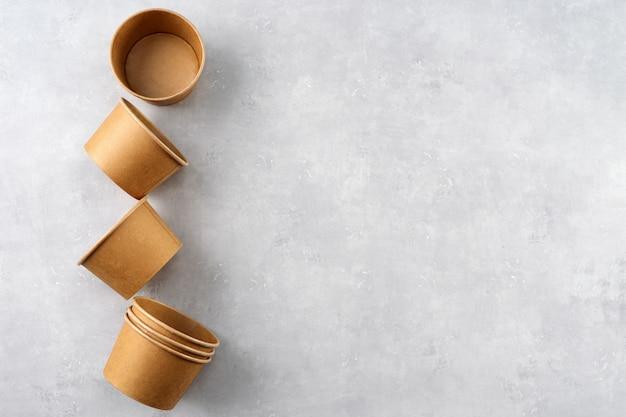 Copos de papel kraft eco em fundo cinza