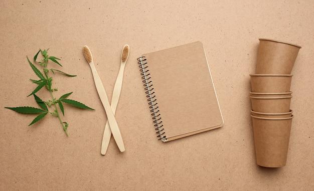 Copos de papel marrom descartáveis, bloco de notas e escovas de dentes ambientais de madeira sobre um fundo marrom, vista superior