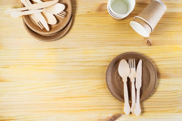 Copos de papel pardo, pratos, talheres de madeira com fundo de madeira