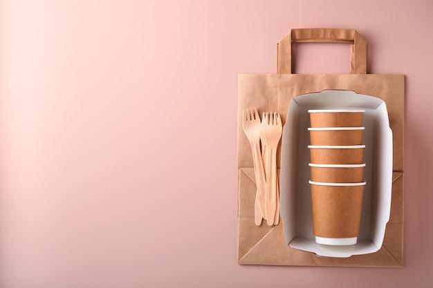 Copos de papel, pratos, bolsa, garfos de madeira, canudos, recipientes de fast food, talheres de madeira em fundo rosa. artigos de mesa de papel eco craft. reciclagem e conceito de entrega de comida. brincar. vista do topo