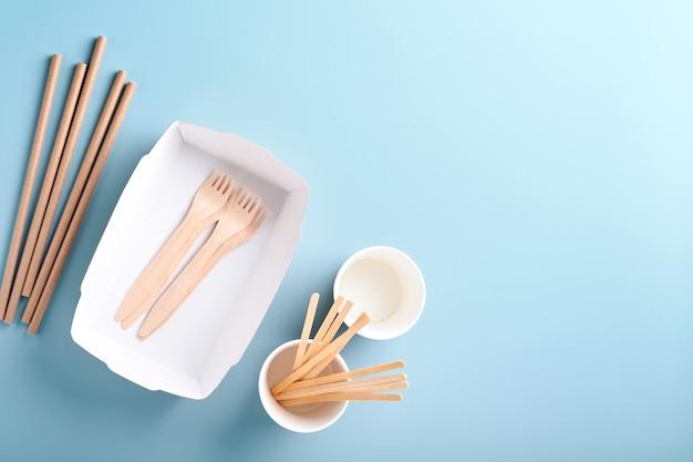 Copos de papel, pratos, bolsa, garfos de madeira, canudos, recipientes de fast food, talheres de madeira sobre fundo azul claro. artigos de mesa de papel eco craft. reciclagem e conceito de entrega de comida. brincar. vista do topo