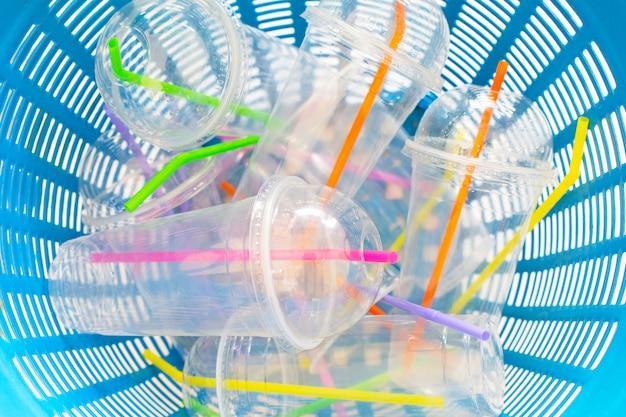 Copos de plástico com canudos no cesto de lixo.