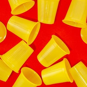 Copos de plástico descartáveis em fundo vermelho