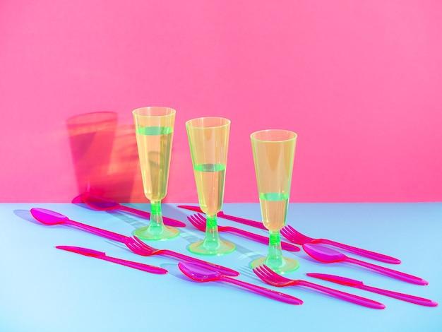 Copos de plástico, facas e garfos isolados em fundo meio azul e rosa, talheres descartáveis., com espaço de cópia