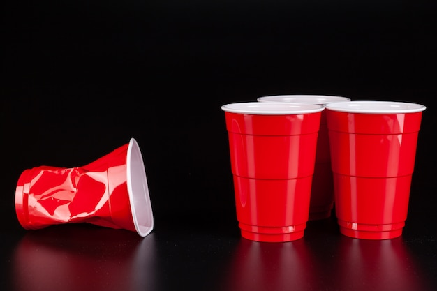 Copos de plástico vermelhos e bola para jogo de pong de cerveja