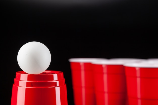Copos de plástico vermelhos e bola para o jogo de pong de cerveja