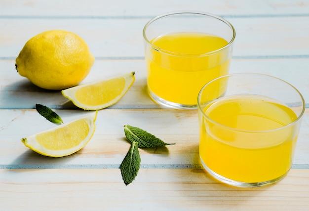 Copos de refrescante bebida amarela perto de limão e hortelã