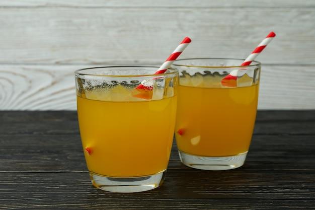 Copos de refrigerante de laranja na superfície de madeira