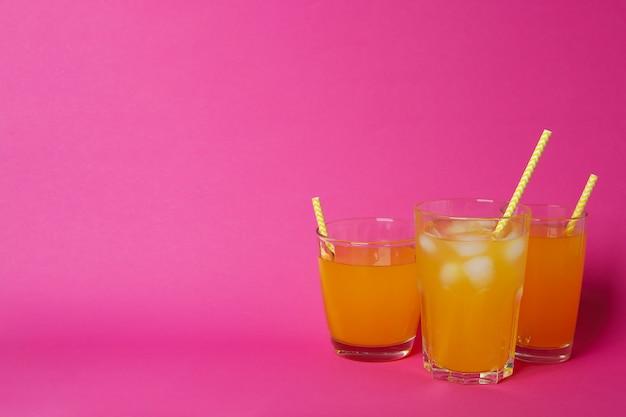 Copos de refrigerante de laranja na superfície rosa