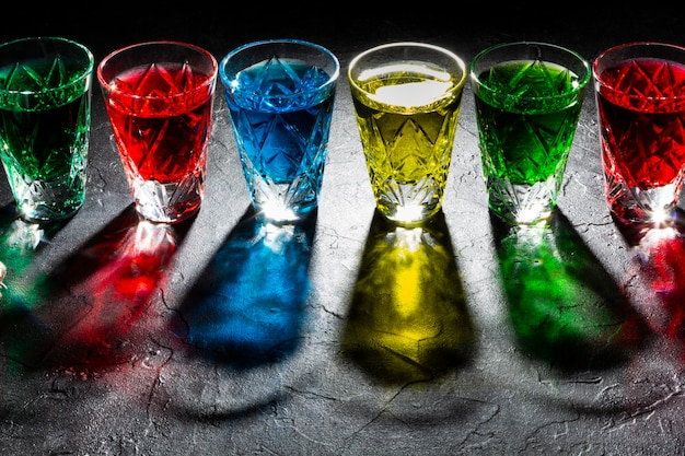 Copos de shot multicoloridos com álcool forte. sombras duras