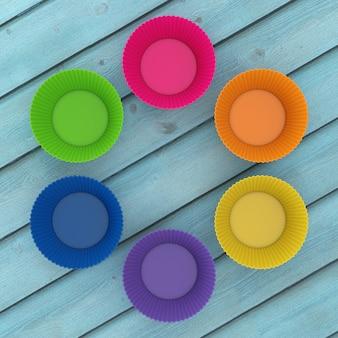 Copos de silicone cupcake colorido em uma mesa de madeira. renderização 3d Foto Premium