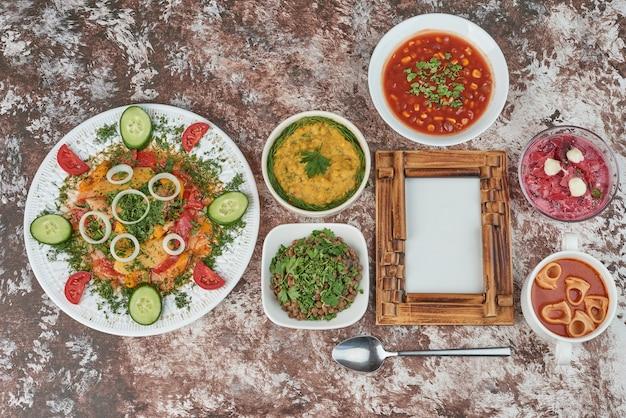 Copos de sopa de salada de legumes em cima da mesa.