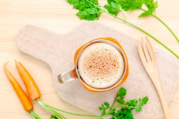 Copos de suco de cenoura com raízes de cenoura em fundo de madeira.