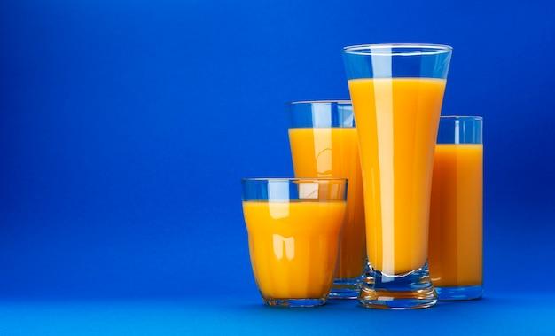 Copos de suco de laranja em fundo azul com espaço de cópia