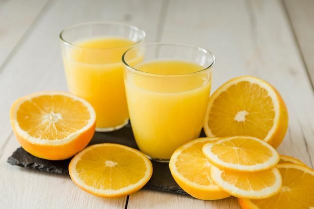 Copos de suco de laranja na placa de ardósia