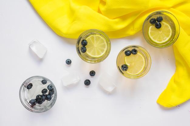 Copos de suco de limão e cubos de gelo com tecido amarelo sobre fundo branco