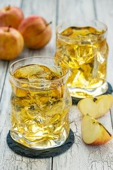 Copos de suco de maçã com gelo e maçã vermelha fresca em uma mesa de madeira em um dia de verão.