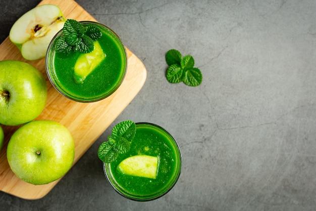 Copos de suco de maçã verde saudável colocados ao lado de maçãs verdes frescas