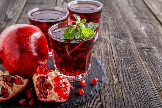 Copos de suco de romã com frutas frescas de romã e hortelã na mesa de madeira.