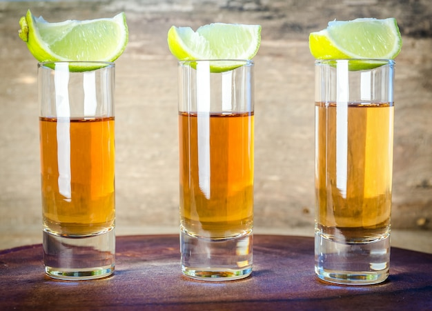 Copos de tequila na tábua de madeira