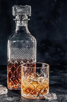 Copos de uísque com uma garrafa quadrada sobre um fundo de pedra preta.