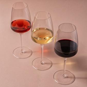 Copos de vermelho, rosa e vinho branco na mesa-de-rosa, vista superior.