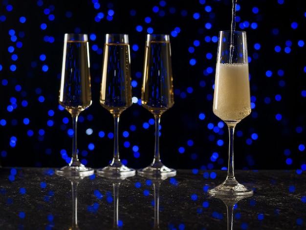 Copos de vidro altos cheios de vinho espumante contra um fundo azul bokeh.