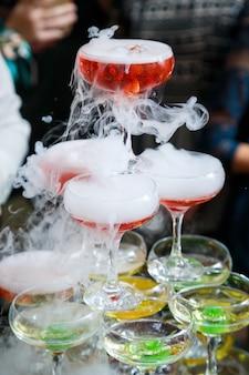 Copos de vidro com bebidas ficam em cima da mesa
