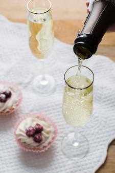 Copos de vinho branco de alta vista e garrafa com cupcakes