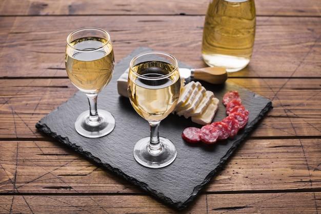 Copos de vinho branco de alta vista e queijo com salame