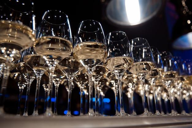 Copos de vinho branco estão sobre a mesa, prontos para servir.