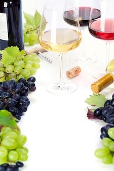 Copos de vinho branco, tinto e rosa e uvas
