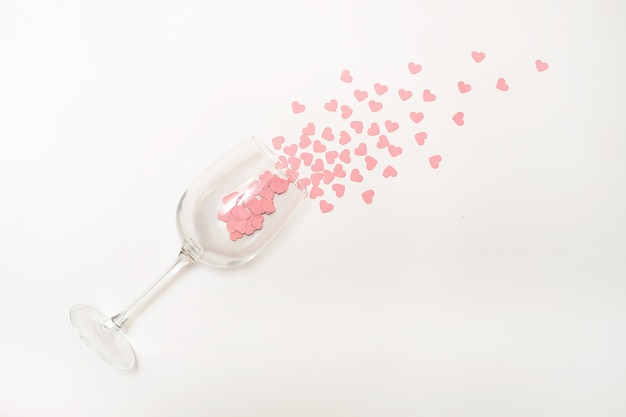 Copos de vinho com confetes cor-de-rosa dos corações no fundo branco. conceito de dia dos namorados