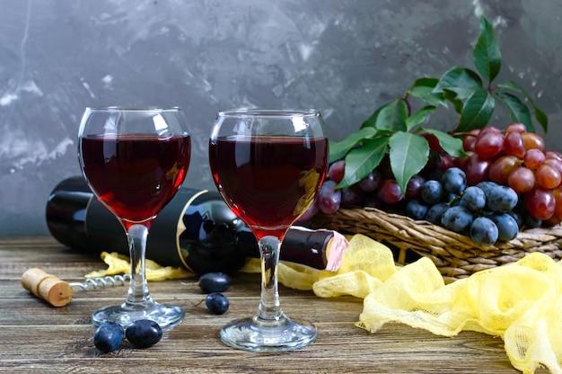 Copos de vinho com vinho tinto, garrafa e uvas frescas