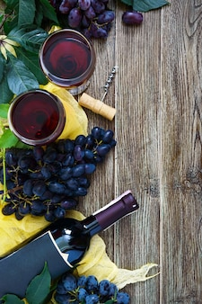 Copos de vinho com vinho tinto, garrafa, saca-rolhas, uvas azuis, folhas sobre uma mesa de madeira. fundo de vinho com espaço de cópia. vista superior, configuração plana