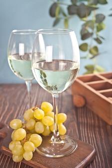 Copos de vinho de uva branca com uvas e caixa de madeira no fundo. vista do topo.