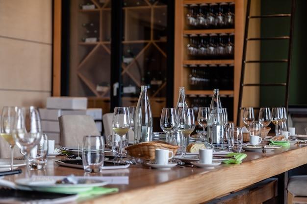 Copos de vinho e água de cristal, pão, xícaras na mesa