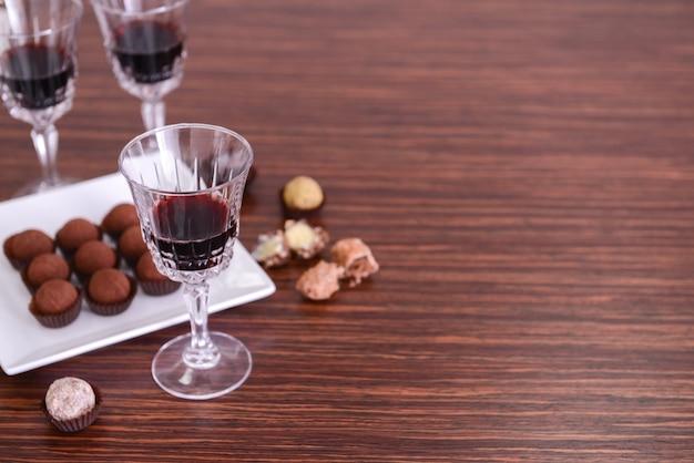 Copos de vinho e chocolates na superfície de madeira