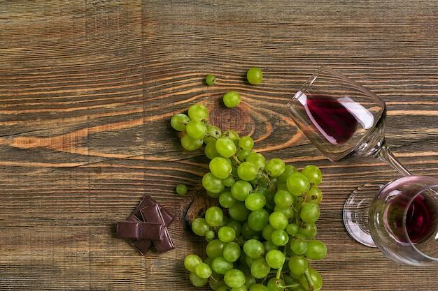 Copos de vinho e uvas maduras, isolados em uma mesa de madeira. vista do topo. copie o espaço. postura plana. natureza morta