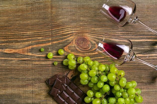 Copos de vinho e uvas maduras isolados em uma mesa de madeira