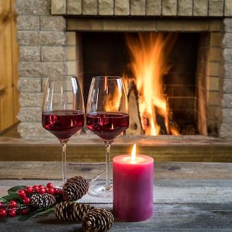 Copos de vinho e velas perto da lareira