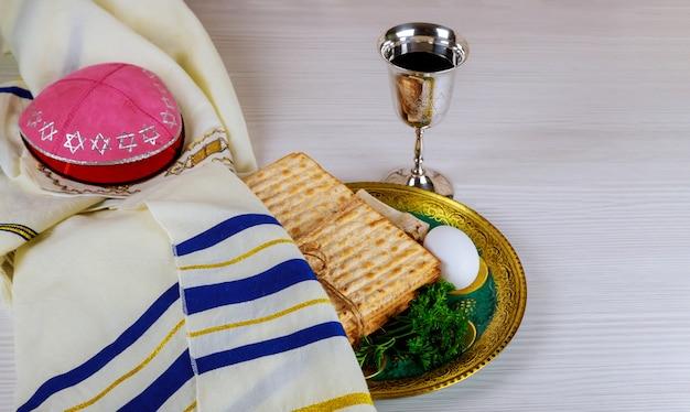 Copos de vinho kosher vermelho de matzah ou matza hagadá de pêssach sobre um fundo de madeira vintage
