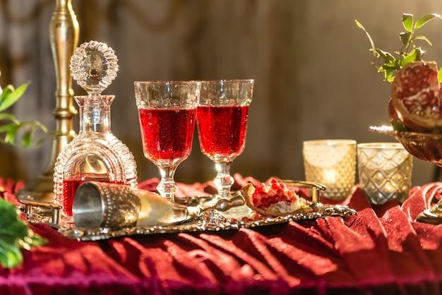 Copos de vinho na mesa vermelha com garrafa