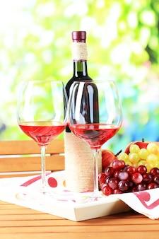 Copos de vinho no guardanapo na bandeja na mesa de madeira na natureza