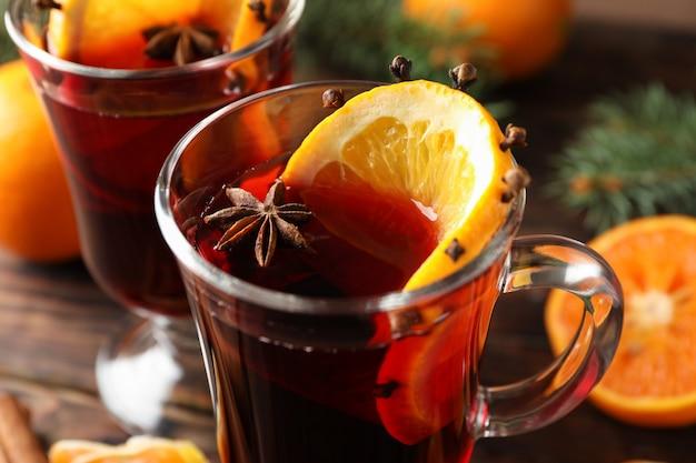 Copos de vinho quente saboroso com laranja na mesa de madeira, close-up