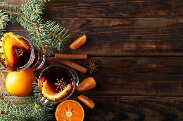 Copos de vinho quente saboroso com laranja na mesa de madeira, vista superior