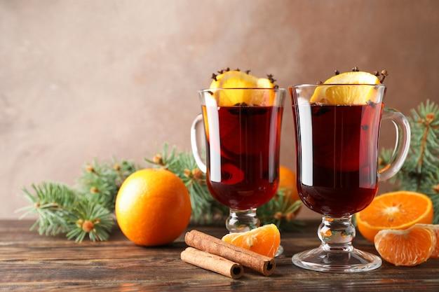 Copos de vinho quente saboroso com laranja na mesa de madeira